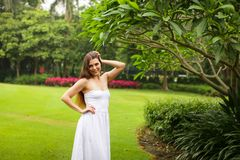 Portrait of carefree young woman in white dress posing in green summer park stock photo