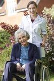 Portrait Of Carer Pushing Senior Woman In Wheelchair Stock Photos