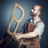 Carpenter with chair. Portrait of carpente holding unfinished chair studio shot stock photos