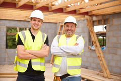Portrait Of Carpenter With Apprentice Working On Site Royalty Free Stock Photography