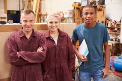 Portrait Of Carpenter With Apprentices In Furniture Workshop Royalty Free Stock Images