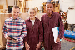 Portrait Of Carpenter With Apprentices In Furniture Workshop Stock Photo