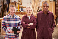 Portrait Of Carpenter With Apprentices In Furniture Workshop Stock Image