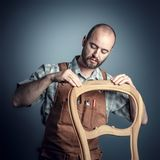Portrait of carpenter. Checking unfinished wood chair,studio shot stock images