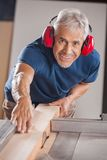 Portrait Of Carpenter Cutting Wood With Tablesaw Stock Photos