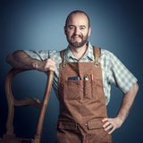 Portrait of carpenter. Smiling carpenter with apron studio shot portrait stock photo