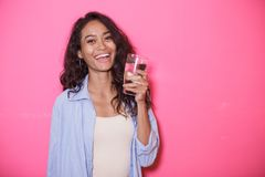 Casual asian woman with a glass of mineral water. Portrait of casual asian woman with a glass of mineral water on pink background Royalty Free Stock Photos