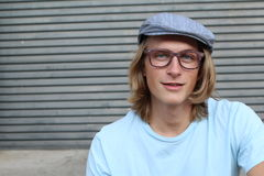 Portrait of casual blonde young man wearing glasses, news paperboy hat and blue crew neck t-shirt.  Stock Image