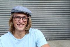 Portrait of casual blonde young man wearing glasses, news paperboy hat and blue crew neck t-shirt smiling and laughing Stock Photography
