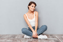 Portrait of a casual happy woman sitting on the floor Royalty Free Stock Images
