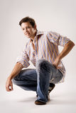 Portrait of a casual male in jeans. Crouching Royalty Free Stock Photography