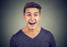Man excited with surprised face expression. Portrait of a casual man looking excitedly at camera shocked happily with news Stock Photo