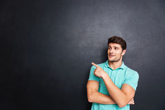 Portrait of a casual man pointing away over black background Stock Images