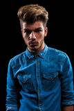 Portrait of casual man wearing denim shirt in dark studio Royalty Free Stock Photography