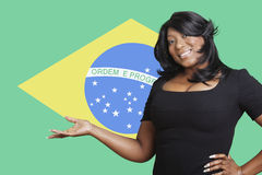 Portrait of casual mixed race woman holding out empty palm over Brazilian flag Stock Photography