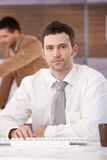 Portrait of casual office worker sitting at desk Stock Photography