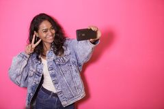 Casual pretty woman taking selfies using mobile phone camera. Portrait of casual pretty woman taking selfies using mobile phone camera on pink background Stock Photos