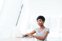 Portrait of a casual smiling african businesswoman using laptop computer Stock Photos