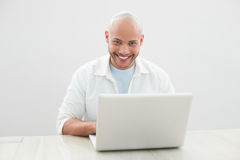 Portrait of casual smiling man using laptop at desk Stock Images