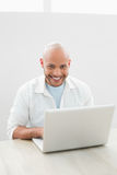 Portrait of a casual smiling man using laptop at desk Royalty Free Stock Image