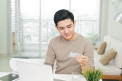 Portrait of a casual smiling young man make payment using credit Royalty Free Stock Images