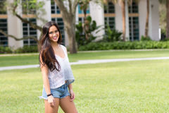 Portrait of a casual smiling young pretty Asian girl outdoors Royalty Free Stock Photography