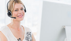Portrait of a casual woman with headset using computer Stock Photography