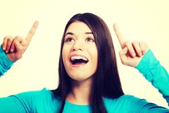 Portrait of a casual woman pointing up. Royalty Free Stock Photography