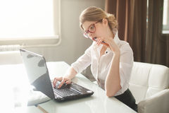 Portrait of a casual young businesswoman. In blouse using laptop computer in office Stock Photography