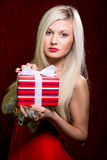 Portrait of casual young happy smiling blonde hold striped gift Royalty Free Stock Photo
