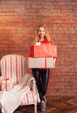 Portrait of casual young happy smiling woman hold gift box again. Portrait of casual young happy smiling woman hold red gift box against a brick wall Royalty Free Stock Images