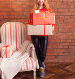 Portrait of casual young happy smiling woman hold gift box again. Portrait of casual young happy smiling woman hold red gift box against a brick wall Royalty Free Stock Photos