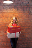 Portrait of casual young happy smiling woman hold gift box again. Portrait of casual young happy smiling woman hold red gift box against a brick wall Stock Photo