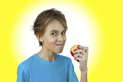 Portrait casual young man eating apple. Against a white wall Stock Photography