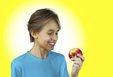 Portrait casual young man eating apple. Against a white wall Stock Photos