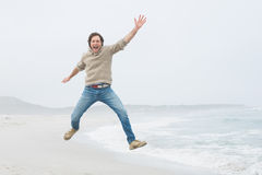 Portrait of a casual young man jumping at beach Royalty Free Stock Photo