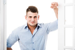 Portrait casual young man leaning against the frame of an open door on light background smiling and looking to camera stock image