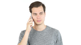Portrait of a casual young man speaking on the phone. white background Royalty Free Stock Photography