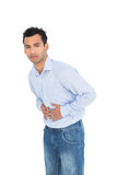 Portrait of a casual young man with stomach pain Stock Image