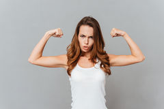 Portrait of a casual young woman showing her muscles Stock Photography