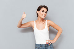 Portrait of a casual young woman showing thumbs up Stock Images