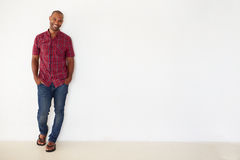 Portrait Of Casually Dressed Man Leaning Against White Wall Royalty Free Stock Photography