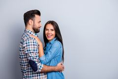 Portrait of caucasian, attractive couple in shirts - man with b. Portrait of caucasian, attractive couple in shirts - men with bristle embrace his charming royalty free stock images