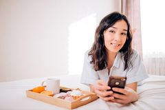 Young woman eating healthy breakfast in bed. Portrait of caucasian attractive girl with phone lying on bed in morning in modern bedroom. Woman smiling enjoying stock photography