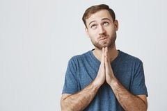 Portrait of caucasian bearded male keeps palms together, has pleading expression, asks for fortune, looks upwards with. Great desire, against gray background stock photo