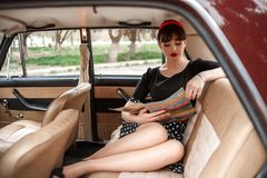 Portrait of a Caucasian beautiful young girl in a black vintage dress, posing in vintage car reading an old magazine.  stock photos