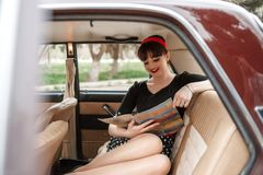 Portrait of a Caucasian beautiful young girl in a black vintage dress, posing in vintage car reading an old magazine.  royalty free stock photography