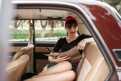 Portrait of a Caucasian beautiful young girl in a black vintage dress, posing in vintage car reading an old magazine.  stock photo