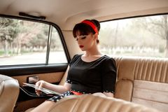 Portrait of a Caucasian beautiful young girl in a black vintage dress, posing in the salon of vintage car reading an old magazine.  royalty free stock images