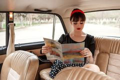 Portrait of a Caucasian beautiful young girl in a black vintage dress, posing in vintage car reading an old magazine.  stock photography
